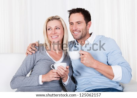 Happy loving young couple enjoying a cup of tea or coffee sitting close together on the sofa laughing with his arm around her