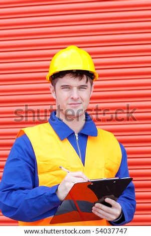 Happy male engineer writing his report at work
