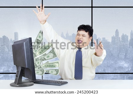 Happy male entrepreneur celebrate his success while working on computer and get money