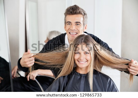 Happy male hairdresser examining female customer's hair at salon
