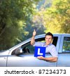 Happy male in his car holding a  L sign and giving thumb up after having his driver's licence - stock photo