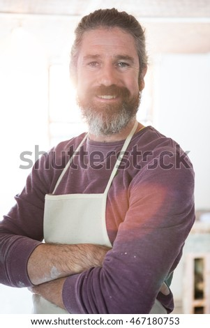 Happy male potter standing with arms crossed in pottery workshop
