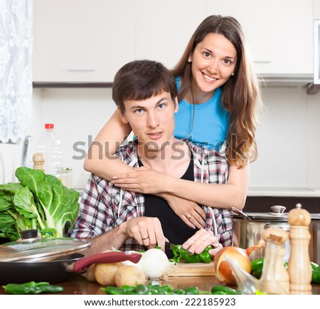 Happy man and  woman cooking food in house kitchen