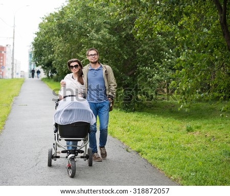 happy man and woman walking with baby pram outdoors
