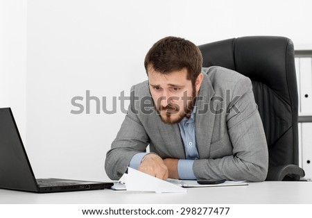 happy man businessman at his desk let a paper airplane