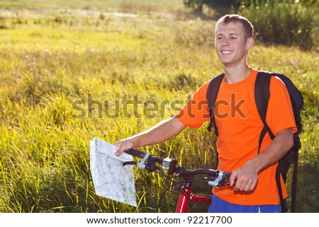 Happy man cyclist with map in hand illuminated by soft sunlight against a background of green nature