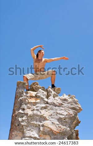 Happy man doing chinese gymnastics on top of mountain. Shot in Krakadouw, Cederberg Mountains, near Clanwilliam, Western Cape, South Africa.