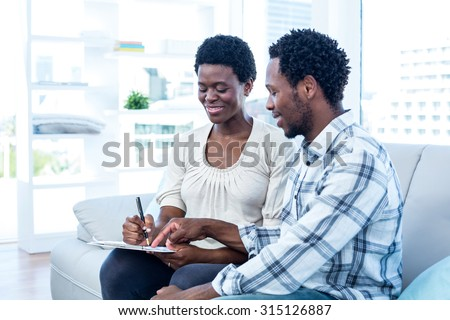 Happy man talking with pregnant wife while pointing on paper at home