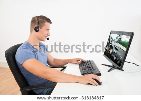 Happy Man With Headset Playing Game On Desktop Computer At Home