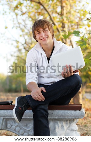 Happy man with laptop sitting in an bench, outdoors autumn