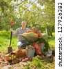 Happy man with vegetables harvest in garden - stock photo