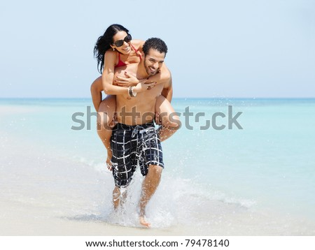 happy maried adult couple having fun and playing on the sea shore in cuba. Horizontal shape, full length, copy space