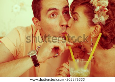 Happy marriage concept. Portrait of a beautiful married couple of hipsters in trendy clothing drinking mojito and kissing in vintage restaurant. Wedding day. Retro style. Close up. Indoor shot