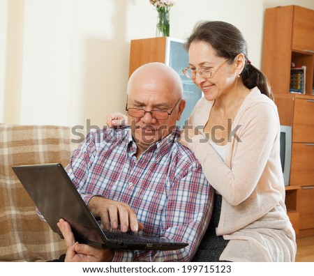 Happy mature couple studying laptop at home