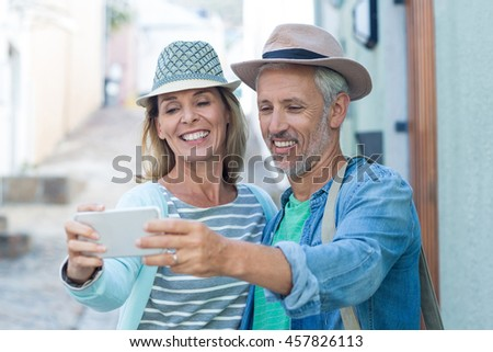 Happy mature couple taking selfie in city