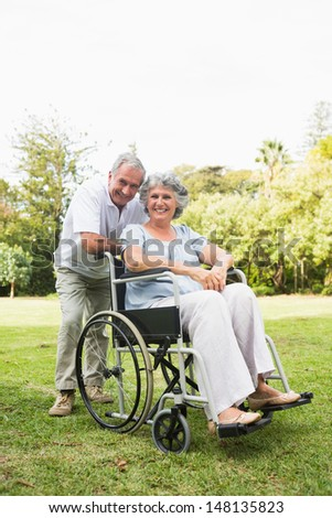 Happy mature woman in wheelchair with partner looking at camera in the park