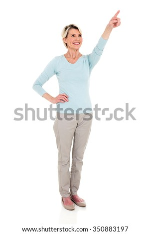 happy middle aged woman pointing at empty copy space isolated on white