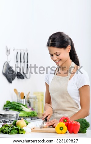 Happy mix race woman cooking and preparing food in the kitchen wearing a apron