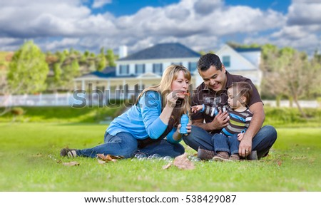 Happy Mixed Race Ethnic Family Playing with Bubbles In Their Front Yard.
