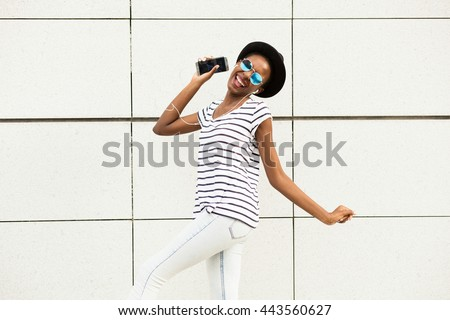 happy modern young black woman with sunglasses, hat and striped shirt  listening music outside and dancing