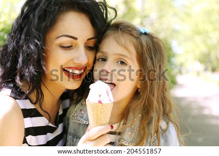 Happy mom and daughter in the green park with ice cream