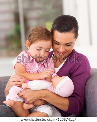 happy mom playing doll with little daughter on sofa
