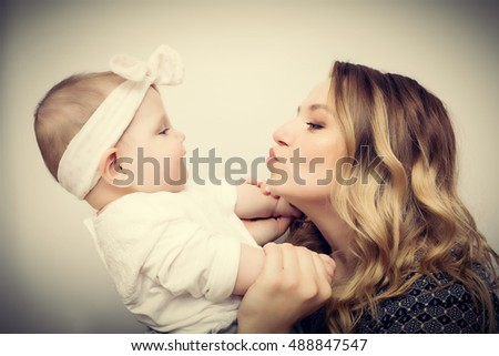 Happy moments. Mother holding and playing with her baby. Motherhood, maternity love concept. Vintage