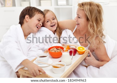 Happy morning - breakfast in bed for mom, kids pampering their mother