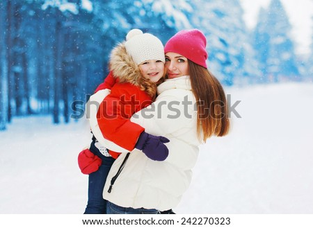 Happy mother and child having fun in snowy day