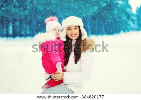 Happy mother and child walking in snowy winter forest