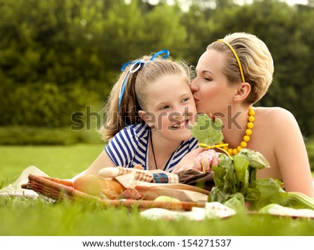 Happy mother and daughter kissing outdoors. Family picnic