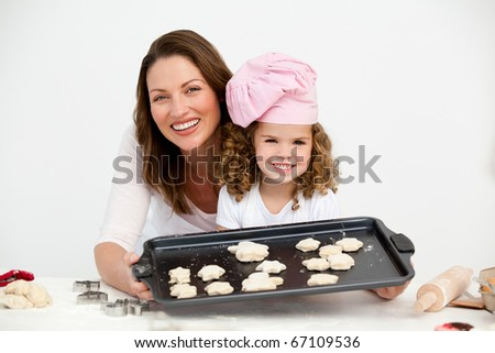 Happy mother and daughter showing a plate with biscuits to the camera