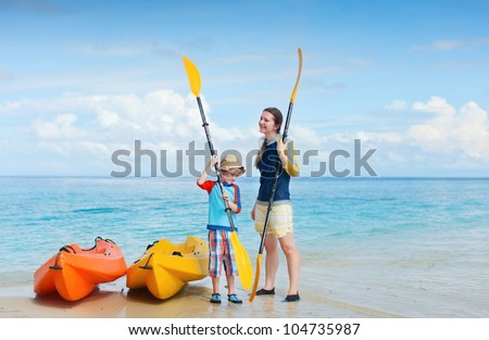 Happy mother and son at beach preparing for kayaking