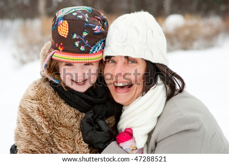 Happy mother with daughter in winter park