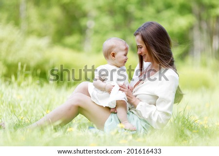 Happy mother with daughter sitting in summer park
