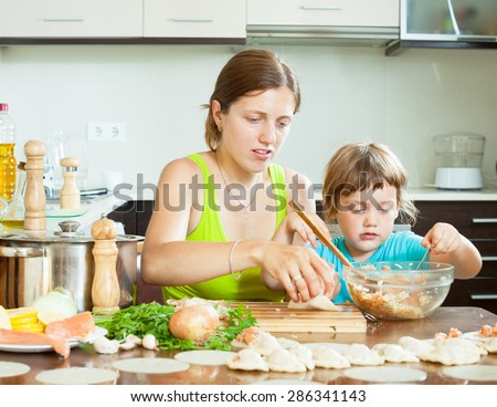 Happy mother with her daughter doing Fish dumplings in a huge house in the kitchen