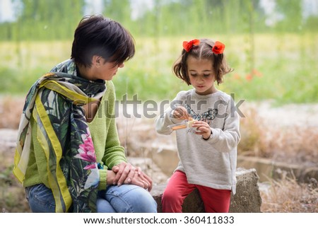 Happy mother with her little daughter picnicking