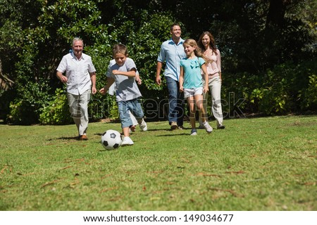 Happy multi generation family playing football together in the park