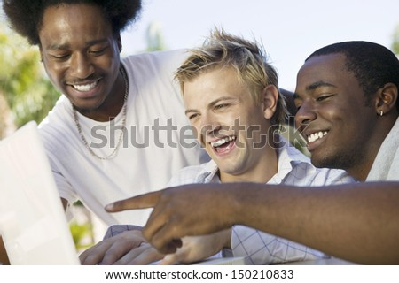Happy multiethnic male friends using laptop outdoors