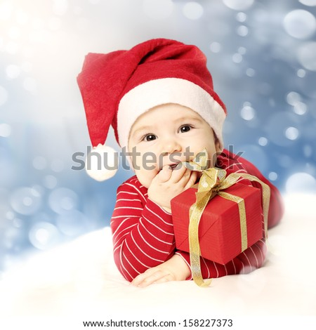 Happy New Year baby with red gift on snow background