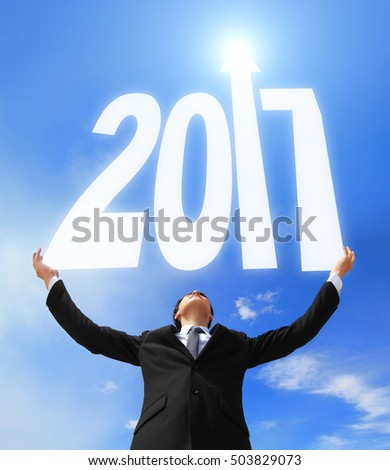 Happy new year - Business man holding 2017 new year imagination with sky and cloud, asian