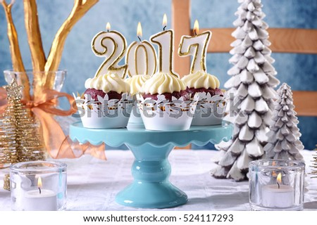 Happy New Year 2017 cupcakes on a modern stylish, festive, blue gold and white Winter theme table setting, closeup on cakestand.