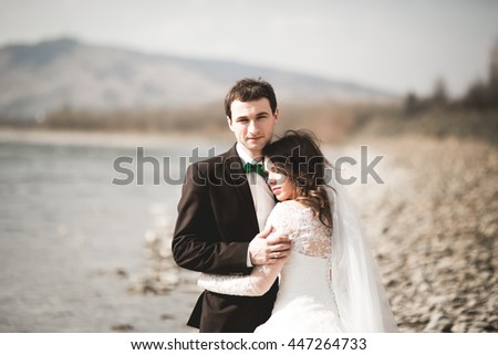 Happy newlyweds, bride and groom posing on river with beautiful views