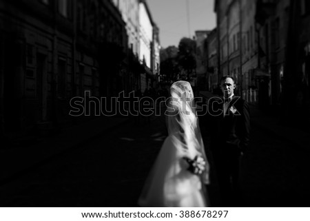 Happy newlyweds walking on the crowded city street on their wedding day. Black and white art wedding portrait.