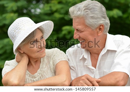 happy old couple walks in the park in summer day