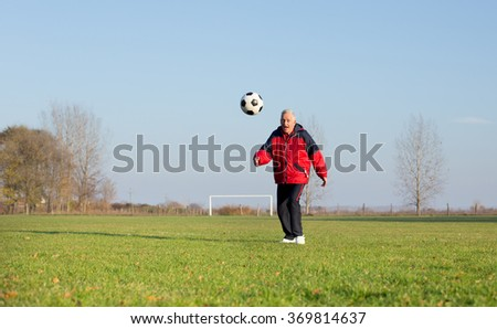 Happy old man in seventies kicking a soccer ball on the grass field