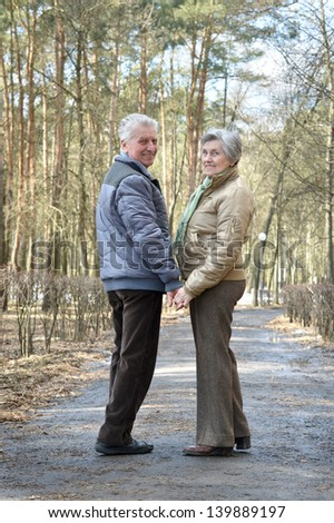 happy older couple on a walk in the forest in the spring