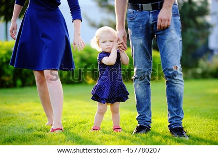 Happy parenthood: young parents with their sweet toddler girl in sunny park. The whole family dressed in the same color scheme. Family style clothing.