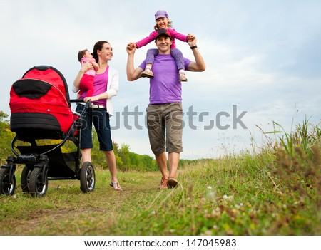 happy parents are walking with their little daughters  in park
