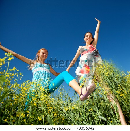 Happy people jumping in field